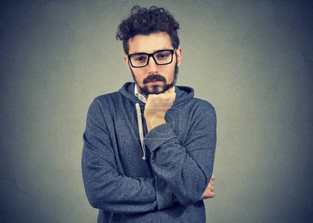 Photo for Young casual man in contemplation looking worried while looking down and solving problem in mind. - Royalty Free Image