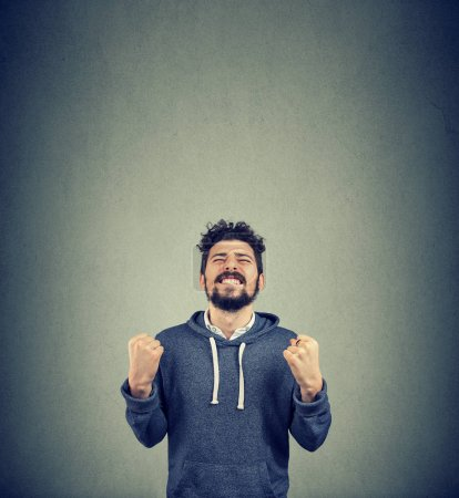 Photo for Happy successful student man winning, fists pumped celebrating success isolated on wall background. Positive emotion face expression. Life achievement - Royalty Free Image