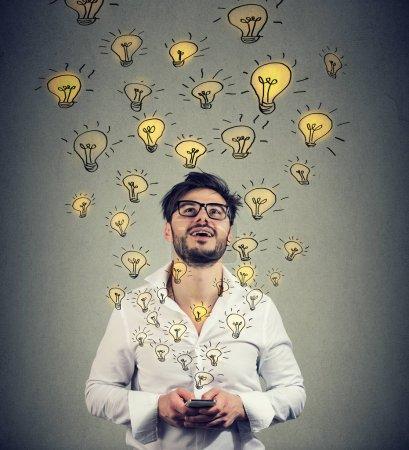 Foto de Joven con gafas de vista sosteniendo smarpthone y produciendo un montón de ideas exitosas . - Imagen libre de derechos