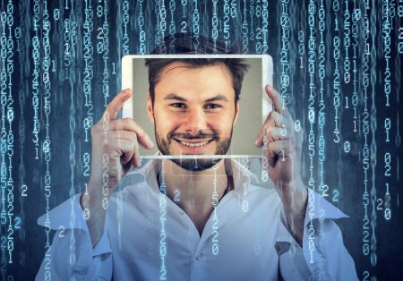 Man holding tablet with his face displayed on a screen on binary code background