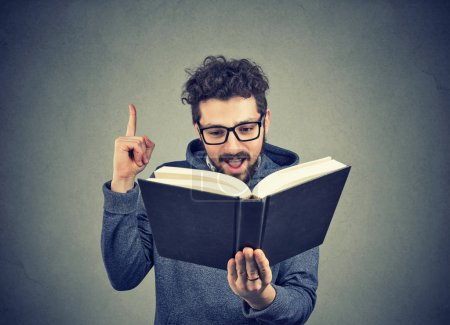 Photo for Excited hipster guy reading a book has a good idea - Royalty Free Image