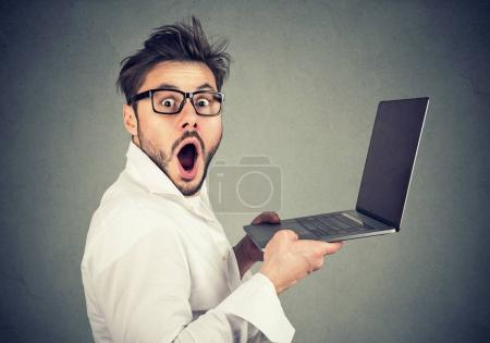 Photo for Side view of young man in eyeglasses looking with mouth opened at camera looking shocked while using laptop. - Royalty Free Image