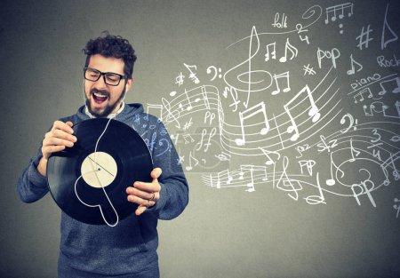 Photo pour Homme décontracté heureux avec disque vinyle écouter de la musique chanter - image libre de droit