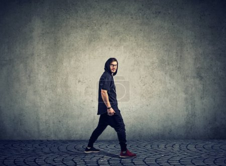 Photo for Side view of stylish hip-hop dancer in glasses walking in sportswear looking at camera. - Royalty Free Image