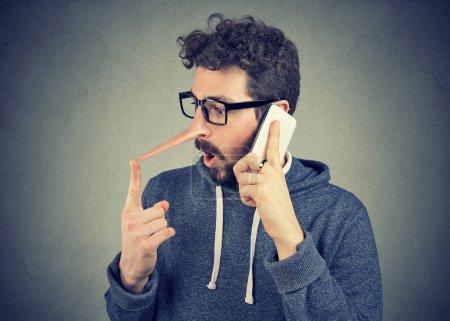 Photo pour Surpris de jeune homme au long nez parler téléphone mobile isolé sur fond de mur. Concept de menteur. Traits de caractère de sentiments émotions humaines - image libre de droit
