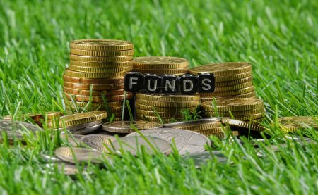 Coins and FUNDs word on green background. Business and saving co