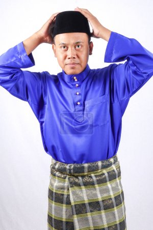 Photo pour Jeune homme asiatique avec une tenue complète de Baju Melayu (Custome national) pour la célébration de l'Aïd Moubarak - image libre de droit