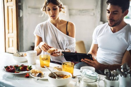 Young beautiful couple with tablet at breakfast