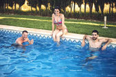 Guys swimming and girl sitting on poolside