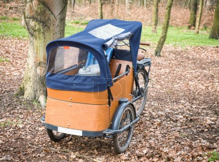 Photo for E-Cargo bike close up in nature. Wooden cargo bike with a tent parking in a forest in Berlin. Background blurred. - Royalty Free Image