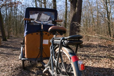 Photo for E-Cargo with battery bike close up in nature. Cargo bike with a tent parking in a forest in Berlin. Background blurred. - Royalty Free Image