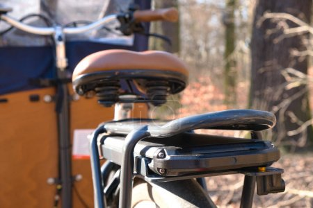 Photo for E-Cargo bike close up in nature with focus on battery. Wooden cargo bike with a tent parking in a forest in Berlin. Background blurred. - Royalty Free Image