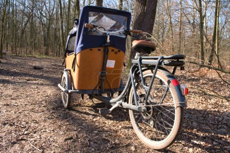 Photo for E-Cargo bike with battery close up in nature. Wooden cargo bike with a tent parking in a forest in Berlin. Background blurred. - Royalty Free Image