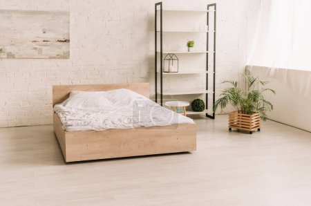 Photo for Interior of spacious, modern bedroom with bed, rack and decorative potted plants - Royalty Free Image