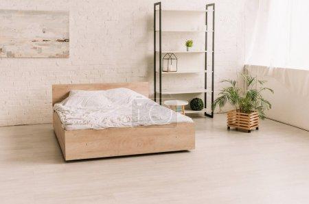 Photo pour Intérieur d'une chambre spacieuse et moderne avec lit, étagère et plantes décoratives en pot - image libre de droit