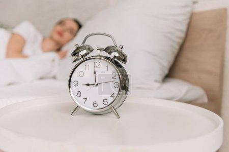 selective focus of vintage alarm clock on bedside table and sleeping woman on background