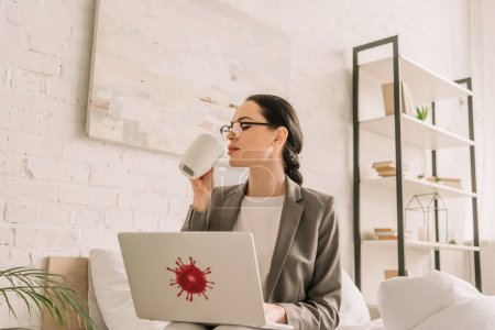 Photo for Attractive businesswoman in blazer over pajamas using laptop and drinking coffee in bedroom - Royalty Free Image