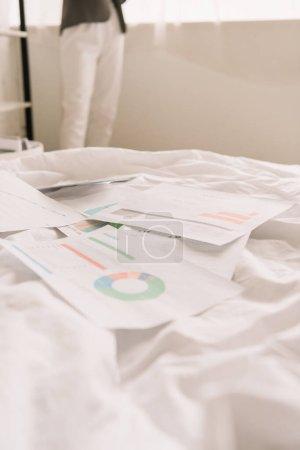 Photo pour Vue recadrée de pigistes et papiers avec graphiques et graphiques sur literie blanche - image libre de droit