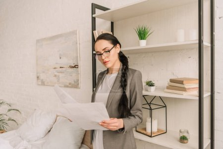 Photo for Attentive businesswoman in blazer over pajamas looking at camera while standing in bedroom - Royalty Free Image