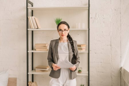 Photo for Confident businesswoman in blazer over pajamas holding papers while looking at camera - Royalty Free Image