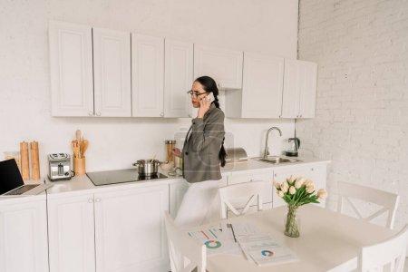 Photo pour Femme d'affaires en blazer sur des pyjamas parlant sur un smartphone pendant la cuisson dans la cuisine près de la table avec des tulipes et des documents - image libre de droit