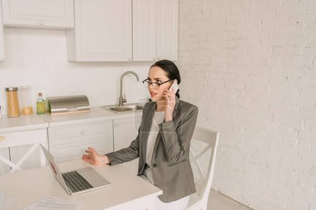 Photo for Young businesswoman in blazer over pajamas talking on smartphone while working in kitchen near laptop - Royalty Free Image