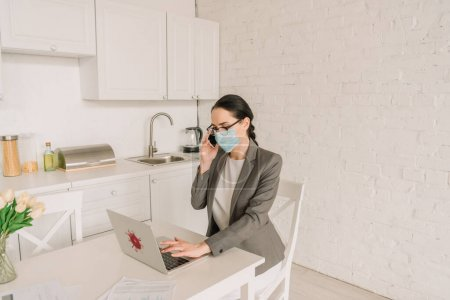 Photo for Businesswoman in medical mask and blazer over pajamas working in kitchen, talking on smartphone and typing on laptop - Royalty Free Image
