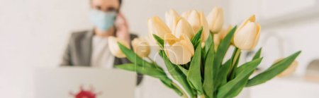 Photo for Selective focus of tulips bouquet near businesswoman in medical mask working at home, horizontal image - Royalty Free Image