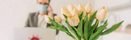 Foto de Enfoque selectivo del bouquet de tulipanes cerca de empresaria en máscara médica trabajando en casa, imagen horizontal. - Imagen libre de derechos