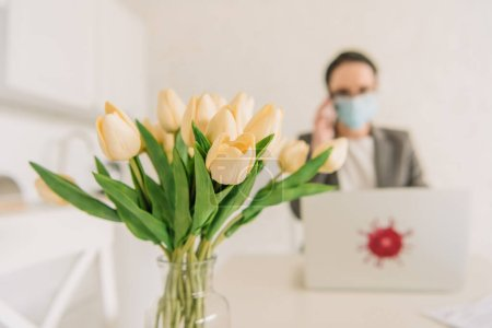 Photo for Selective focus of tulips bouquet near businesswoman in medical mask working at home - Royalty Free Image