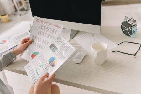 Photo pour Vue recadrée de pigiste regardant des papiers avec des graphiques et des graphiques près de tasse de café et réveil enveloppé dans un masque médical - image libre de droit