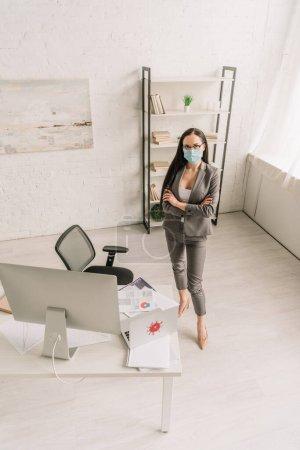 Photo pour Vue à grand angle d'une femme d'affaires en tenue officielle et masque médical debout avec bras croisés près de la table avec des ordinateurs à la maison - image libre de droit