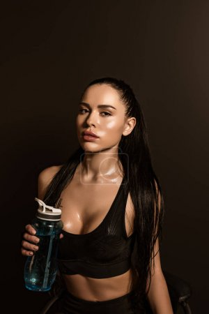 Photo for Sexy sportswoman with sports bottle looking at camera isolated on black - Royalty Free Image