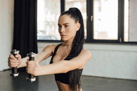 Photo for Beautiful sportswoman holding dumbbells with outstretched hands in gym - Royalty Free Image