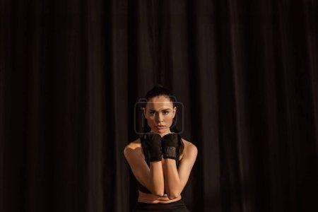 Photo pour Attrayant sportif en gants de sport regardant la caméra sur noir - image libre de droit