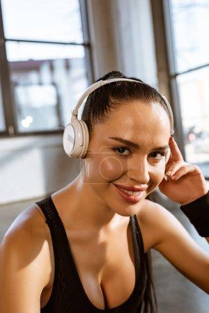 Photo pour Belle sportive en casque souriant et regardant la caméra dans la salle de gym - image libre de droit