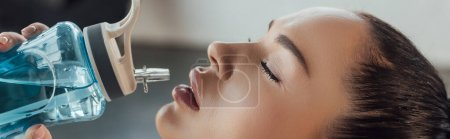 Horizontal crop of sportswoman with closed eyes drinking water in gym
