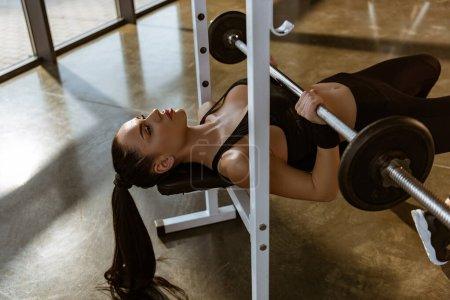 Photo pour Sportswoman sur l'entraînement des équipements sportifs avec haltère dans la salle de gym - image libre de droit