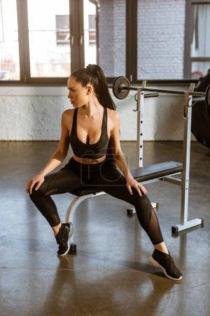 Photo pour Femme sportive sexy assise sur un équipement de sport près de Barbell dans la salle de gym - image libre de droit