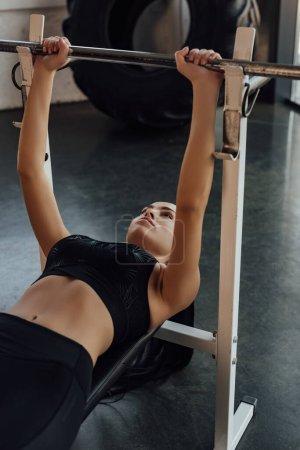 Photo pour Sportswoman couché sur l'équipement sportif et l'entraînement avec haltère dans le centre sportif - image libre de droit