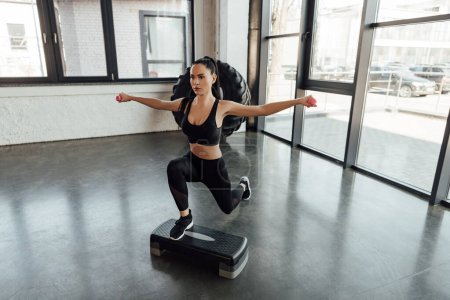 Photo for High angle view of sportswoman with dumbbells working out on step platform in gym - Royalty Free Image