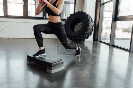 Photo for Cropped view of sportswoman working out on step platform in gym - Royalty Free Image