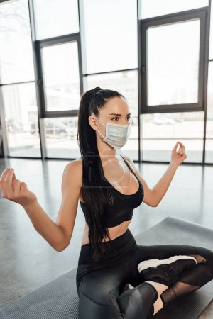 Photo for Sportswoman in medical mask with crossed legs meditating on fitness mat in sports center - Royalty Free Image