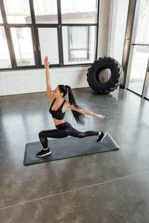 High angle view of sportswoman doing lunges with hand in air on fitness mat in gym
