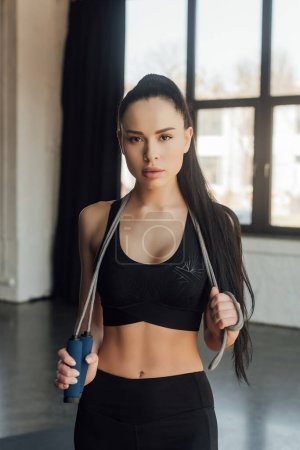 Front view of beautiful sportswoman with skipping rope looking at camera in gym