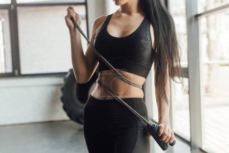 Cropped view of sportswoman with skipping rope in gym