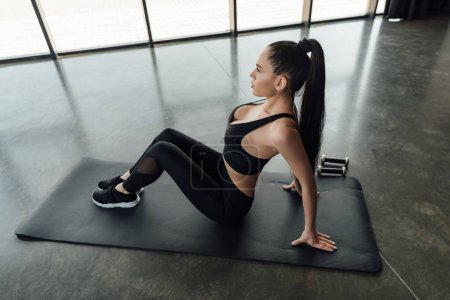 Photo for High angle view of sportswoman sitting on fitness mat near dumbbells in gym - Royalty Free Image