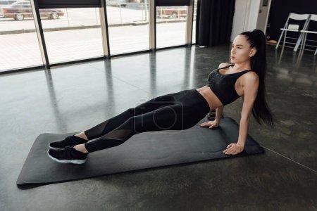 Photo pour Brunette sportive faisant planche sur tapis de fitness dans le centre sportif - image libre de droit