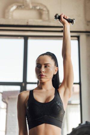 Photo pour Attrayant sportif regardant loin et tenant haltère avec la main dans l'air dans la salle de gym - image libre de droit