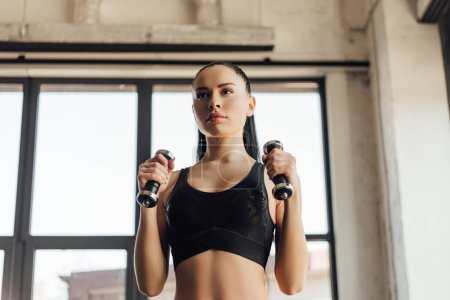 Photo for Attractive sportswoman in sports top holding dumbbells in gym - Royalty Free Image